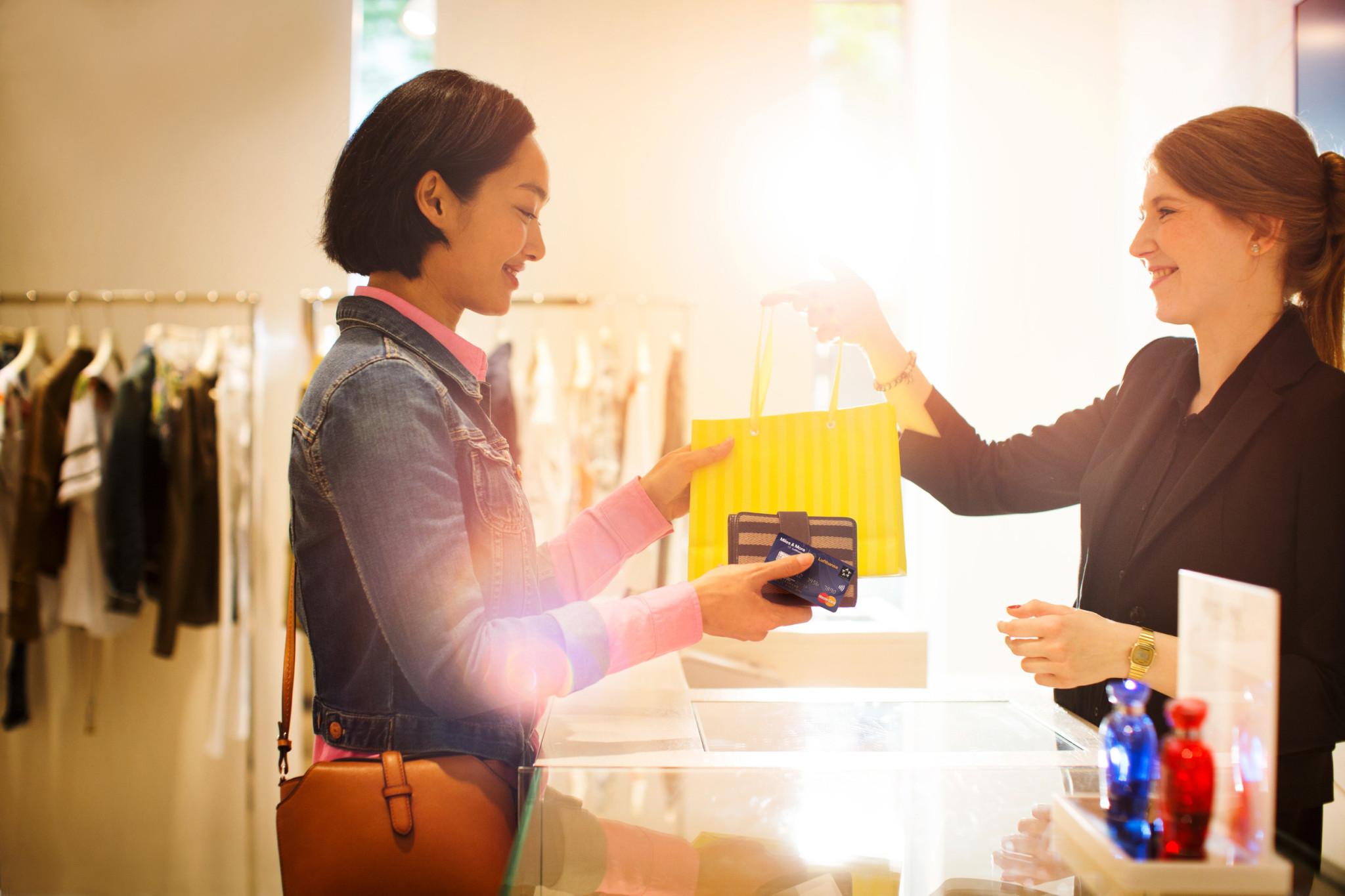 Shopping-Begeisterte sammeln beim Stadtbummel extra Prämienmeilen, wenn sie mit der Miles & More Kreditkarte bezahlen